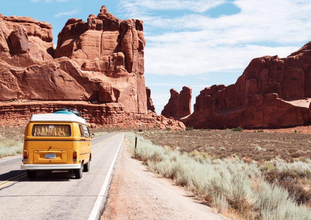 Volksyellow Wagen converted van drives in front of red rock desert