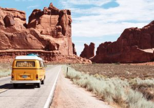 Volksyellow Wagen converted van drives in front of red rock desert