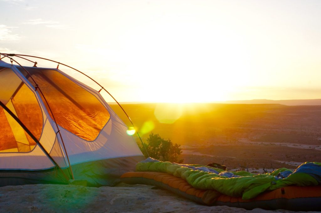 orange tent camped at sunrise with sleeping bags outside